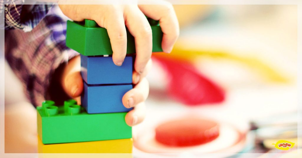 a kid's hand with a green lego-like blocks