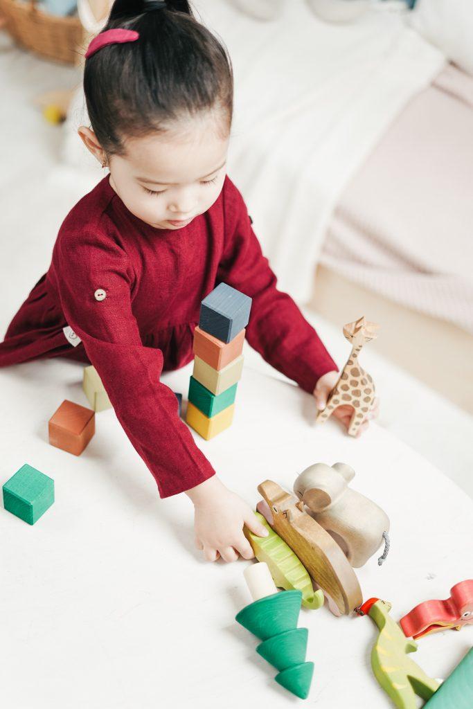 Bambina asiatica gioca con giocattoli di legno